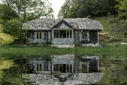Haunted House. The dilapidated house on the waterfront. Abandoned house. Water reflection. Lake. Swamp