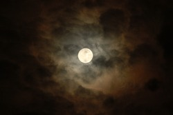 Haunted night with bright full halloween moon in the sky surrounded by spooky and scary dark orange cloud.  Serenity nature background, outdoor at nighttime before lunar eclipse.