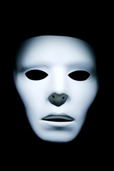 Haunting appearance of a white ghost like face against a black background.