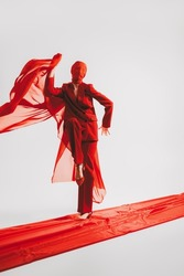 Haute couture fashion. A stunning fashion model poses in motion in red clothes and a cloth on her head on the red carpet on a white background. Studio portrait. Copy space.