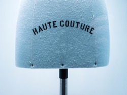 Haute Couture signage on mannequin made from fine luxury garment textile in luxury fashion store atelier