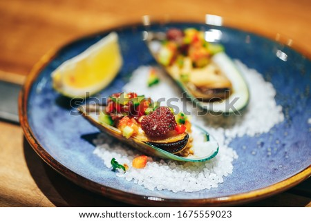 haute cuisine delicious fresh oysters with vegetables decoration on sea salt and blue modern plate in a modern luxury restaurant Photo stock ©