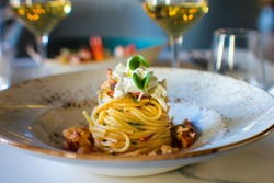 haute cuisine dish with spaghetti with lobster, buffalo stracciatella and a fine white wine. In a luxurious Italian restaurant