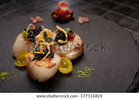 Haute cuisine 3 scallops served on black plate. Close-up.