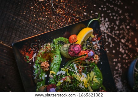 Haute cuisine vegetarian plate of appetizer rolls and a bowl of herbs served on a wooden table next to salt grinder in a restaurant Photo stock ©