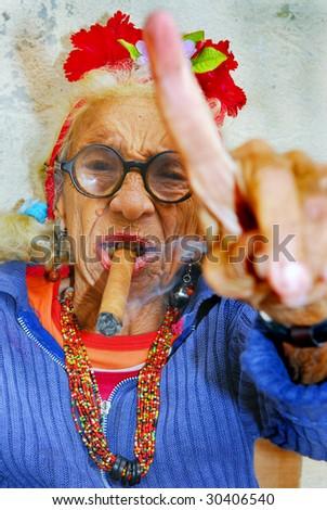 HAVANA – CIRCA DECEMBER 2008: An eccentric old Cuban lady smokes cigar and points finger circa December 2008 in Havana, Cuba.