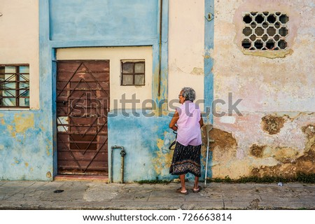 HAVANA, CUBA, CIRCA APRIL 2017: Old cuban woman walking down the streets of Havana. With its shabby atmosphere Havana attracts over 1 million tourists every year.