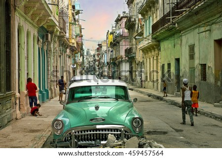 HAVANA, CUBA - CIRCA JULY 2016: People walking along a historic street in Havana, Cuba afternoon by a shiny classic old American car
