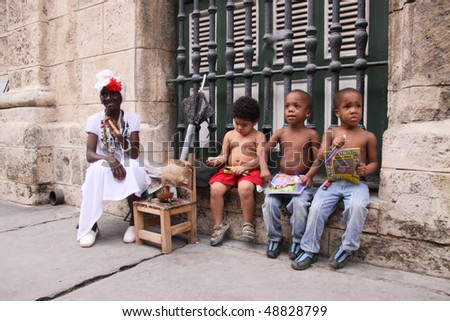 HAVANA, CUBA - FEB 24: kids playing with some cartoon books and a old woman posing for a photo in the streets of havana  February 24, 2010 in Havana, Cuba.