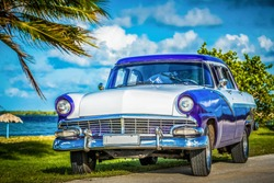 Havana, Cuba - June 30, 2017: American blue white Ford Fairlane classic car parked on the Malecon near the beach in Havana Cuba - Serie Cuba Reportage