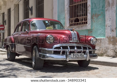 HAVANA, CUBA - JUNE 13, 2014: Red old american car parked in front of a colonial house in Old Havana.