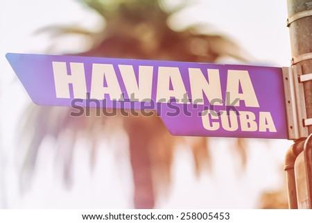 Havana Cuba Street Sign. A street sign marking Havana, Cuba. Backed by a palm tree with a sunset flare.