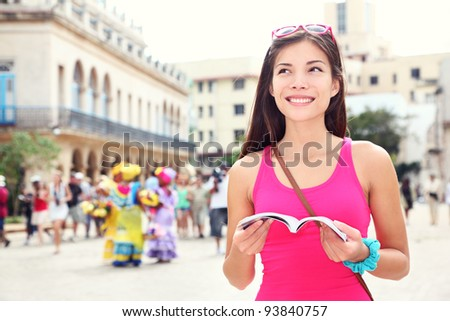 Havana, cuba - tourist with travel guide book on Plaza de Armas, Havana, Cuba. Young woman traveler smiling happy.