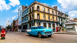 Havana, Cuba. Vintage classic American car on the streets of the famous vibrant vibrant capital also known as Habana. A spontaneous moment  of cheerful tourists enjoying their beautiful vacation.