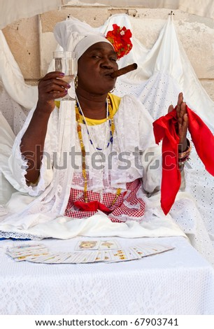 HAVANA-DECEMBER 24:Lady with a fine cigar wearing typical clothes and afrocuban religious necklaces  practicing cartomancy December 24, 2010 in Havana.