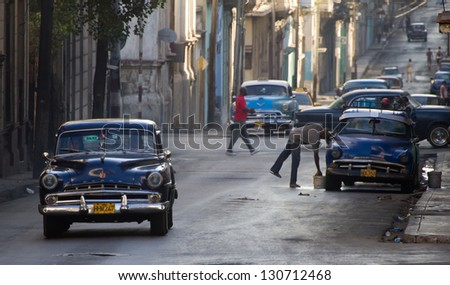 HAVANA - JANUARY 13: Classic cars riding in a street on January 13, 2013 in Havana. These old and classic cars are an iconic sight of the island