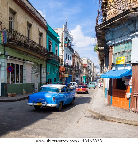 HAVANA-SEPTEMBER 13:People and old cars in a central street September 13,2012 in Havana.With 2.4 million inhabitants in the city and 3.7 in its urban area,Havana is the largest city in the Caribbean