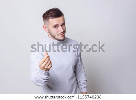 Have a money concept. Portrait caucasian man making cash sign gesture rubbing fingers together on grey background copy space #1155740236