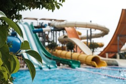 Have fun riding slides in an aquapark. Summer vacation entertainment ideas. Colorful slide variety and turquoise swimming pool at a hotel. Water reflection in empty aqua park during pandemic isolation
