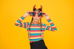 Have funny Halloween. Party girl look through funny star shaped glasses. Funny child with spooky look. Creepy and funny. Halloween celebration. Holiday season.