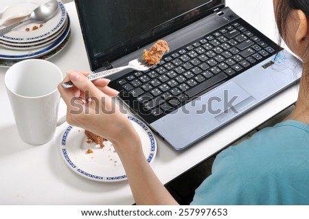 have lunch while busy and using laptop among stack of dirty plates , selective fork focus