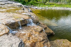 Havelock Conservation area featuring Healey Falls step cascade on a sunny summer day with water streaming through yellow stones