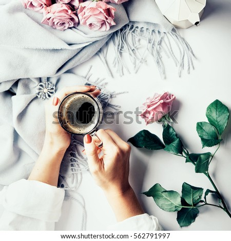 Having a break: female hands holding cup of coffee. Flatlay with wool scarf and pink roses. Overview.