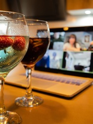 Having a couple of cocktails with friends during a video call during the pandemic