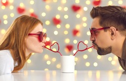 Having a fun date on Saint Valentine's Day. Young man and woman leaning over cafe table and sipping drink from one cup through heart-shaped straws enjoying cute and funny couple moment