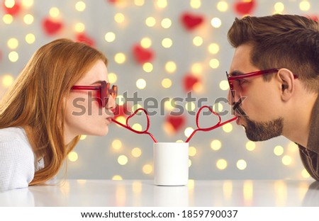 Having a fun date on Saint Valentine's Day. Young man and woman leaning over cafe table and sipping drink from one cup through heart-shaped straws enjoying cute and funny couple moment Stock photo ©