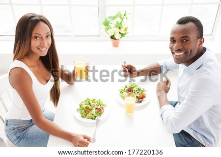 Having a healthy breakfast. Top view of beautiful young African couple sitting together at the table and eating salads with orange juice