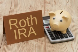 Having a Roth IRA plan, A golden piggy bank, card and calculator on wood background with text  Roth IRA