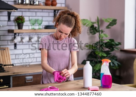 Having allergic reaction. Distressed young woman taking off rubber pink gloves while discovering red spots on her hands #1344877460