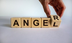 Having anger or being an angel. Hand turns a cube and changes the word 'anger' to 'angel'. Beautiful white background. Business concept. Copy space.