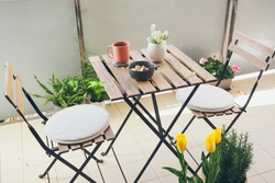 Having brunch - healthy vegan home made bowl with nuts and cacao at home on the apartment balcony. The terrace is beautifully decorated with spring flowers and lots of flower pots. Lifestyle photo