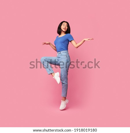 Having Fun. Full body length portrait of happy young asian woman jumping, dancing and looking aside at free space, being in a good mood, isolated over bright pink background, studio shot