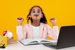 Having Fun. Funny black girl holding pencil between nose and lips as mustache, taking break from study and homework, sitting at desk with laptop isolated over yellow studio wall, banner