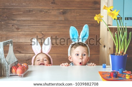Having fun on Easter egg hunt. Child boy and girl wearing bunny ears and painting eggs. colorful eggs.