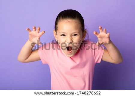 Having Fun. Playful little asian girl imitating tiger, roaring and grimacing over pastel purple studio wall Сток-фото ©