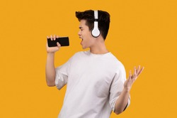Having Fun. Portrait of overjoyed asian guy singing song and using smart phone as microphone, wearing wireless headset. Carefree young man dancing isolated over orange studio background