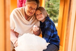 Having fun together. Cheerful grandmother and her blonde attractive grandson laying with head on her shoulder eating cotton candy at the kid train at the park