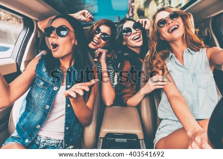 Having fun together. Four beautiful young cheerful women looking happy and playful while sitting in car