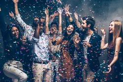 Having fun together. Group of beautiful young people throwing colorful confetti and looking happy