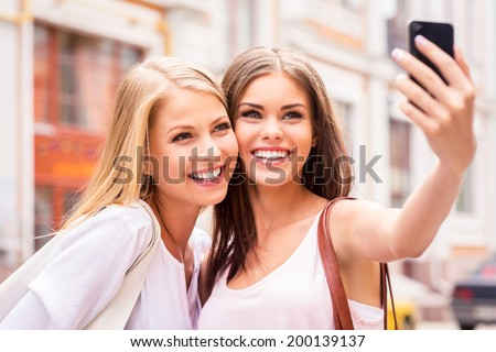 Having fun together. Two beautiful young women making selfie and smiling while standing outdoors