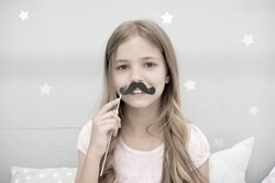 Having fun with fake mustache. Happiness and humor concept. Kid long hair happy smile face. Girl carefree child having fun with mustache. Play with mustache photo booth props. Hair care and beauty