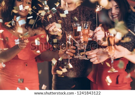 Having good mood and nice time. Multiracial friends celebrate new year and holding bengal lights and glasses with drink. #1241843122