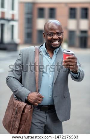 Having good mood. Businessman wearing glasses drinking morning coffee and having good mood