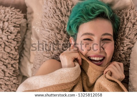 Having good mood. Pleasant appealing green-haired woman having good mood in the morning lying in bed