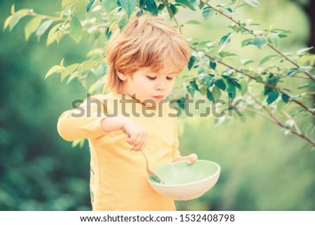 Having great appetite. Organic nutrition. Healthy nutrition concept. Nutrition habits. Kid hold spoon. Small child enjoy homemade meal. Nutrition for kids. Little toddler boy eat porridge outdoors.