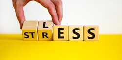 Having less stress or being stress-less. The word 'STRESS' and 'LESS' on wooden cubes. Male hand. Beautiful yellow table, white background, copy space. Business and psychological less stress concept.